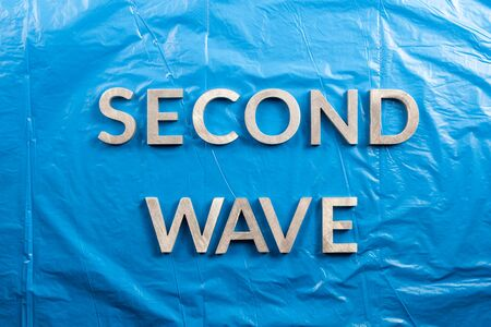 the words second wave laid with silver metal letters over crumpled blue plastic film background. Imagens