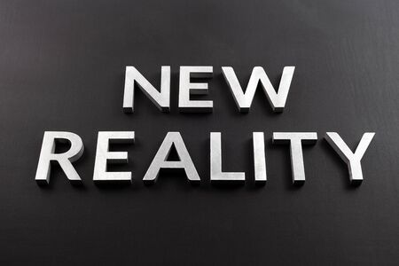 the words new reality laid with silver metal letters on flat black matte surface in slanted linear perspective.