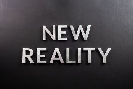 the words new reality laid with silver metal letters on flat black matte surface in straight flat lay perspective.