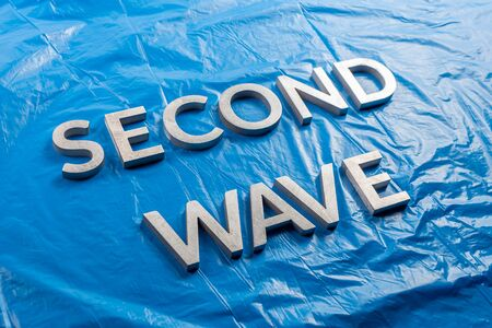 the words second wave laid with silver metal letters over crumpled blue plastic film background in slanted diagonal perspective