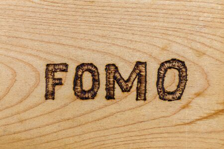 abbreviation FOMO - fear of missing out - burnt by hand on flat wooden surface. Stock fotó - 146743618
