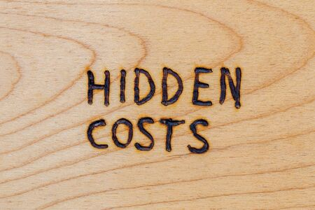 the words hidden costs handwritten with woodburner on flat wood surface - directly above flat lay view