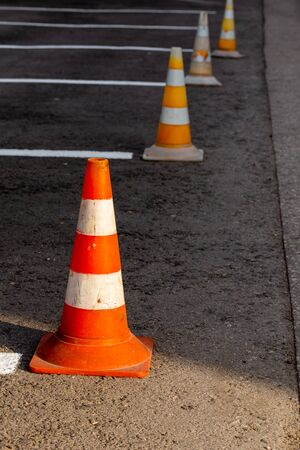 Orange road cones on a asphelt driving area with white lines