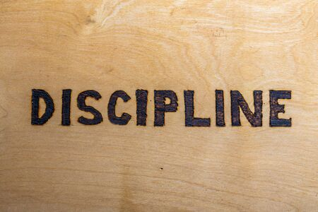 the word discipline burnt on white flat wooden surface - directly above normal view