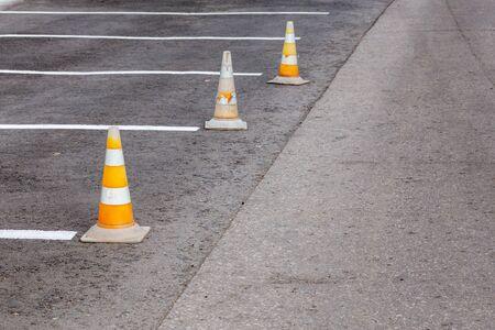 Orange road cones on a asphelt driving area with white lines 版權商用圖片 - 148160631