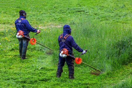 two lawnmower men with string trimmer and face mask trimmong grass - close-up