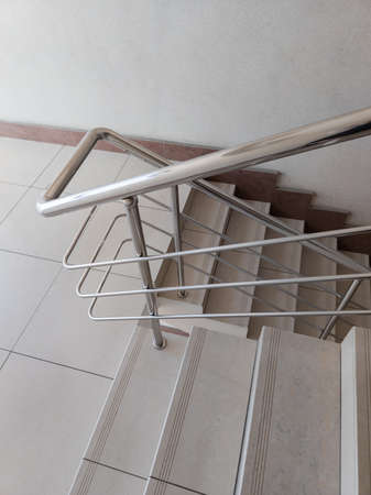 modern design of stanless steel pipes handrail and ceramic tiles staircase in abstract public building