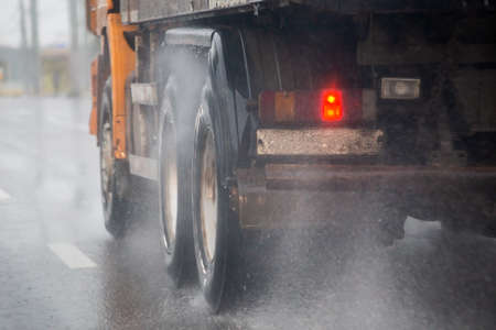 Rain water splash flow from wheels of heavy truck moving fast in daylight city with selective focus. Stock Photo