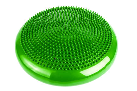 Green inflatable balance disk isoleated on white background, It is also known as a stability disc, wobble disc, and balance cushion.
