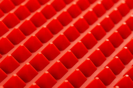abstract red silicone pyramids array close-up background
