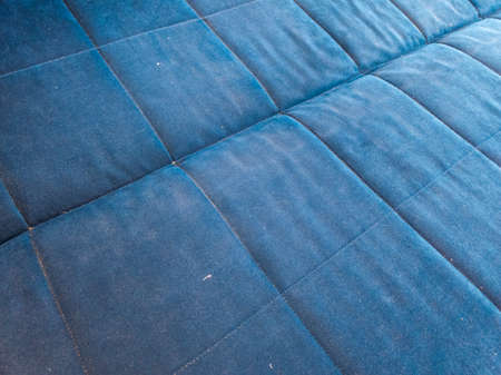 flat surface of dusty blue bed or sofa - closeup with selective focus