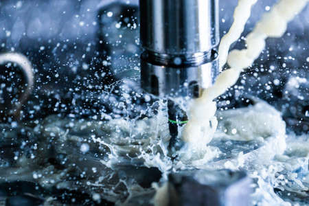 Close-up view of vertical cnc steel milling process with external water coolant streams, splashes and a lot of metal chips, high contrast Stock fotó