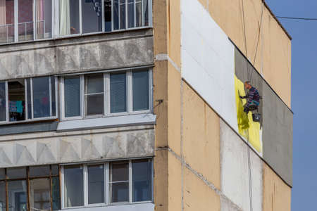 TULA, RUSSIA - OCTOBER 10, 2020: Industrial climber worker applying additional styrofoam insulation on outside wall of nine-storey apartment building 新闻类图片
