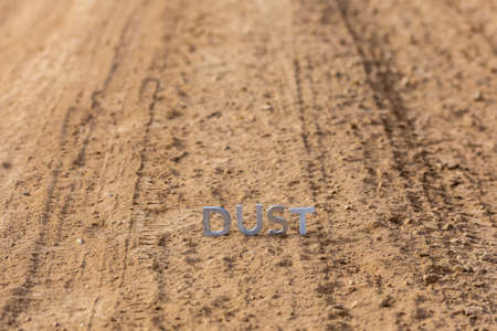 the word dust standing on dusty road surface in linear perspective