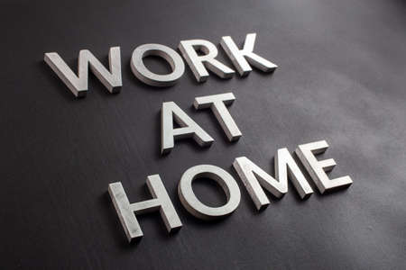 the words work at home laid with silver metal letters on matte black background in diagonal perspective