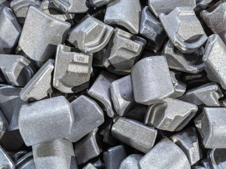 heap of gray steel forgings after shot blasting - close-up natural heavy industrial pattern with selective focus