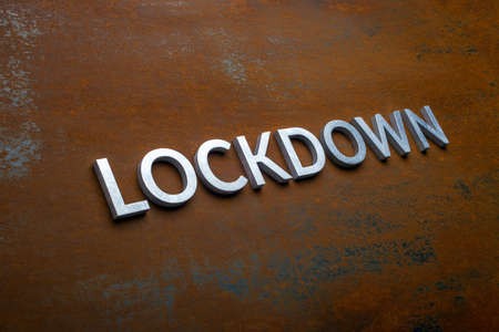 the word lockdown laid with silver metal letters on flat rusted steel sheet background in slanted diagonal perspective Stock Photo