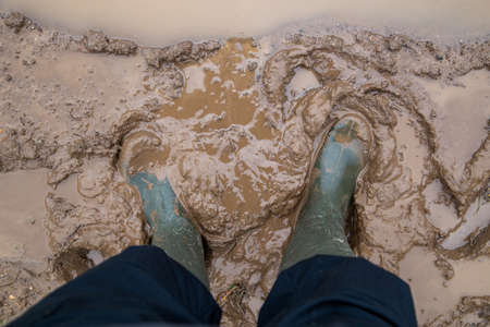 feet in green rubber boots stands in wet brown mud directly above view