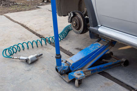 Car without wheel lifted with hydraulic floor jack and pneumatic impact wrench in a outdoor car workshop. Season tire changing procedure.