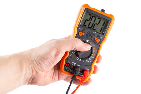 digit 2021 on lcd screen of digital electrical multimeter in left hand, isolated on white background