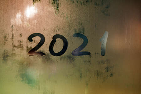 digit 2021 handwritten on wet night window glass surface