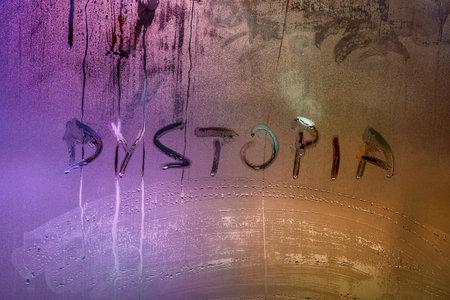 the word dystopia handwritten on wet window glass surface