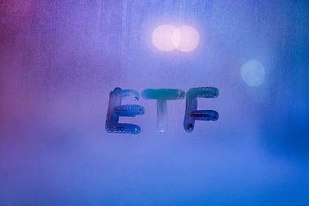 abbreviation word etf - exchange traded funds - handwritten on foggy glass window at night with neon blue back street light