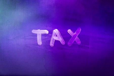 word tax hadwritten on night wet window glass surface