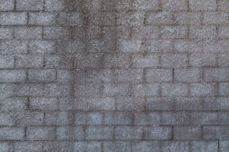 wall of cinder blocks covered with a layer of shagreen concrete plaster