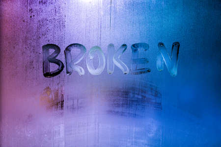 the word broken handwritten on wet window glass