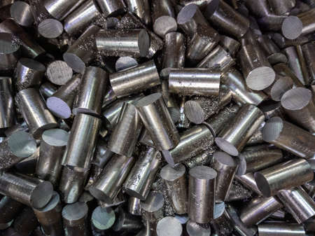 a pile of sawed stainless steel rod chunks - full frame close-up industrial background