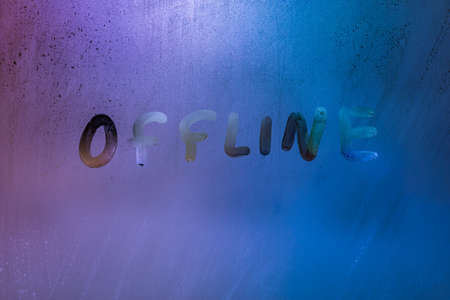 word offline handwrittern on foggy glass with cold neon blue back light