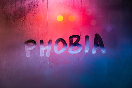 the word phobia handwritten on wet foggy window glass surface with red-blue background lights