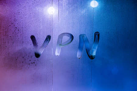 an abbreviation VPN - virtual private network drawed by finger on night wet glass