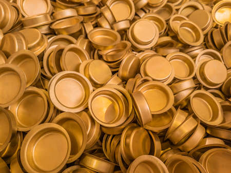 pile of stamped thin sheet brass hat-shaped semimanufatures, closeup with selective focus and blur 版權商用圖片