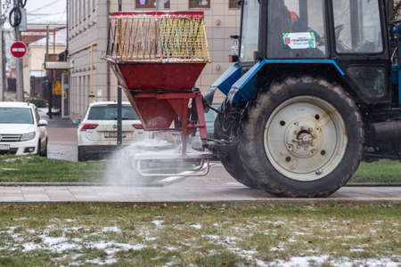 TULA, RUSSIA - NOVEMBER 21, 2020: Tractor spreading salt reagent on city pavement at winter daylight.