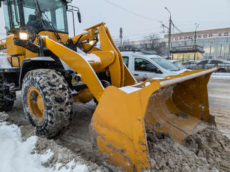 TULA, RUSSIA - NOVEMBER 21, 2020: Tractor with large scoop cleaning snow on road at winter day light. 新聞圖片