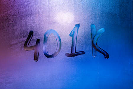 the word 401k - an employer-sponsored defined-contribution pension account plan - handwritten on night foggy window glass
