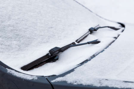car windshield and wiper waterblades frozen and covered with snow at winter cloudy day light