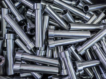 pile of shiny steel tubes after cnc turning operations - abstract full frame indistrial background