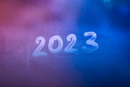 number 2023 handwritten on wet night window glass surface 版權商用圖片