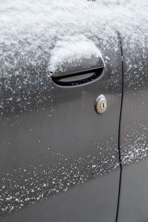 dry dirty and snowy black car door with keyhole of mechanical lock