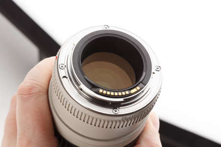 hand holding old white telephoto lens with visible bayonet and rear element Stock fotó