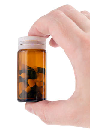 caucasian hand holding brown glass bottle with medical pills inside Фото со стока