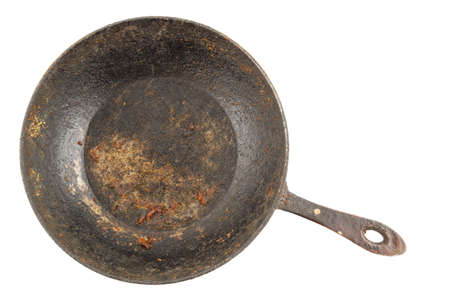 old disgusting stained rusty cast iron pan with burnt fat isolated in directly above perspective