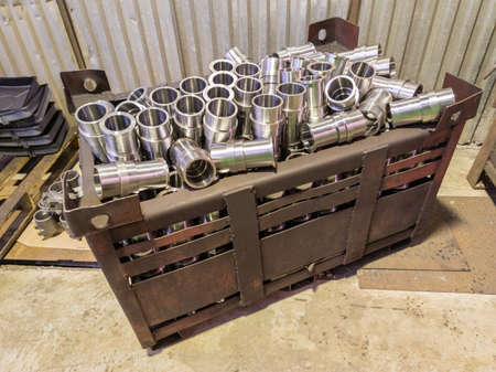 shiny steel cylindrical parts after turning operations overflowing big intermodal steel container box on factory floor