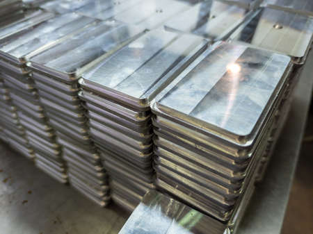 stacks of shiny metal tiles after cnc surface milling Фото со стока