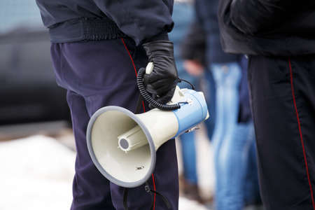 police officer holding loudspeaker megaphone outdoors, close-up Фото со стока