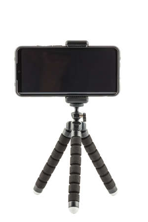 black cellphone in rugged rubber protective cover on small flexible tripod isolated on white Фото со стока