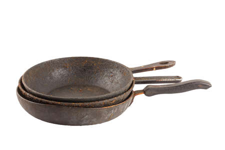 old disgusting stained rusty cast iron pan stack with burnt fat and food leftovers isolated